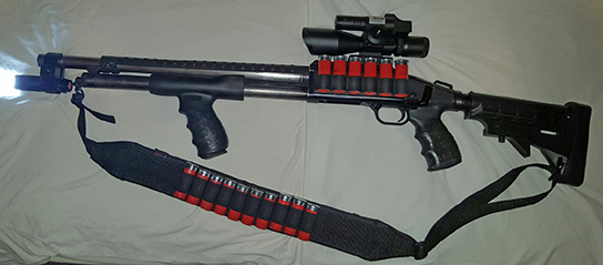 Mossberg Maverick 88 with 18.5 defense barrel, Trinity Supply 6 position tactical stock with pistol grip and Death Grip by TUFF1,Tac Star side saddle with rail mount, Vector optics 2.5-10x40 scope with green high visibility laser and red dot reflex sight combo, Tac Star tactical pistol grip forend with Death Grip by TUFF1, Polymer heat shield by John Masen, Iprotec barrel clamp with 7w 600lm Cree 5 mode flashlight and Ace Case 10 shot bandolier.